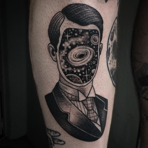 Vintage style black ink mystical man portrait with space without face tattoo on leg