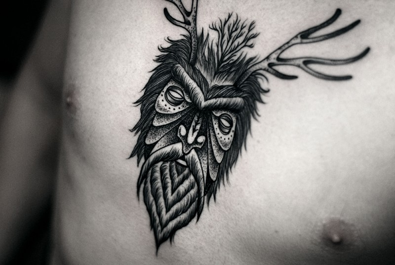 Vintage style black ink mystical man portrait tattoo on chest stylized with deer horns