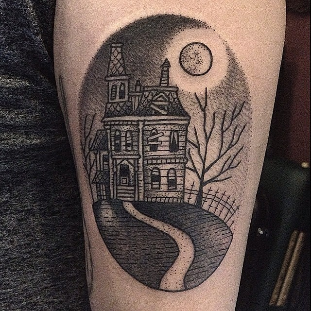 Vintage style black ink oval shaped tattoo on forearm stylized with old abandoned house