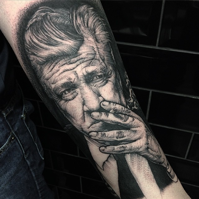 Vintage style black ink smoking man portrait tattoo on forearm