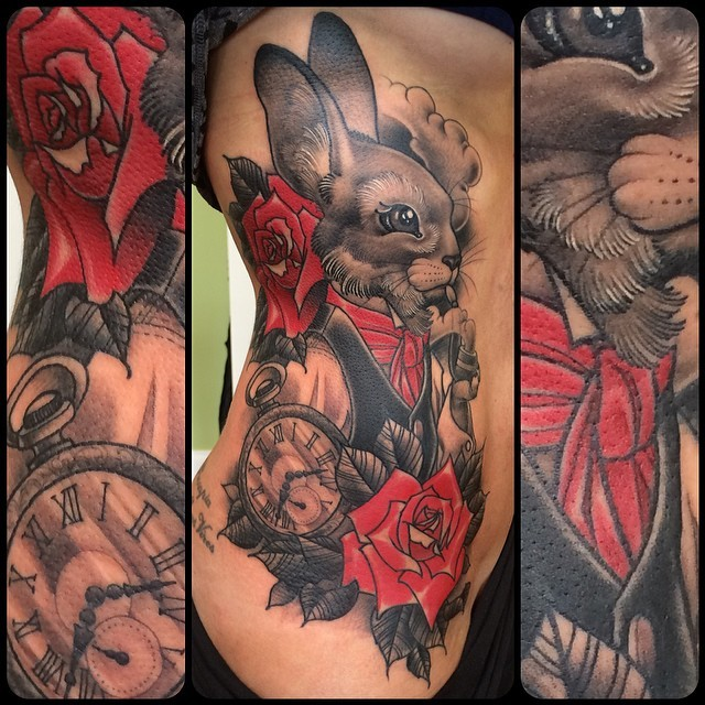 Vintage style colored cute rabbit tattoo on side combined with red rose and clock