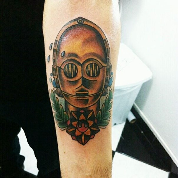 Vintage style colored funny C3PO head tattoo on forearm with flower