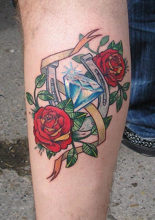 Vintage style colored leg tattoo of horseshoe with flowers
