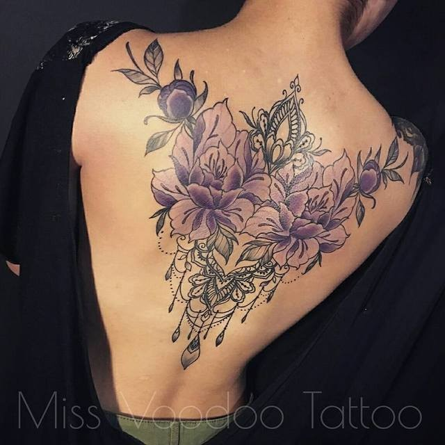 Vintage style colorful whole back tattoo of violet flowers with jewelry by Caro Voodoo