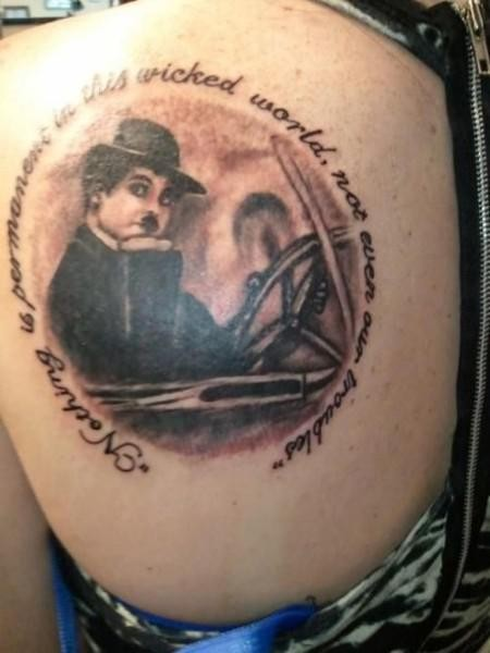 Vintage style detailed thigh tattoo of Charlie Chaplin with lettering