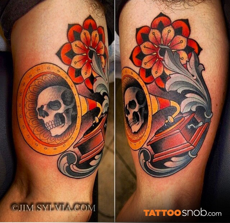 Vintage style multicolored gramophone tattoo on biceps stylized with ornamental flower and skull