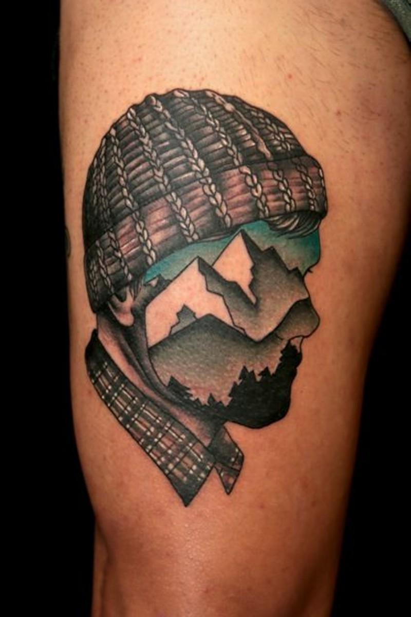 Vintage style painted and colored half portrait half mountains picture tattoo on thigh