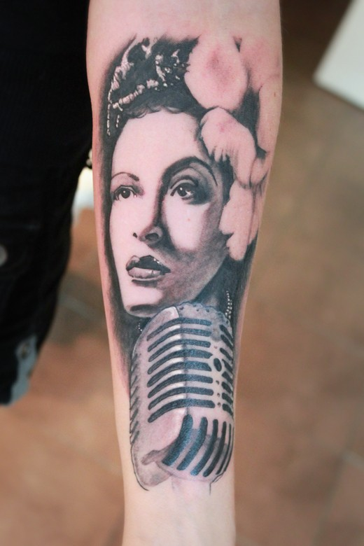 Vintage style painted black and white woman portrait tattoo on forearm with mycrophone
