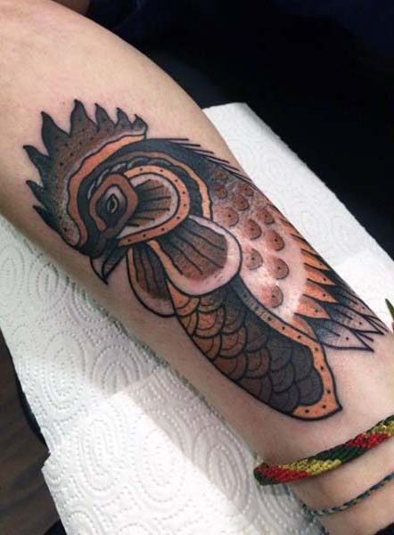 Vintage style painted colored sad cock tattoo on arm