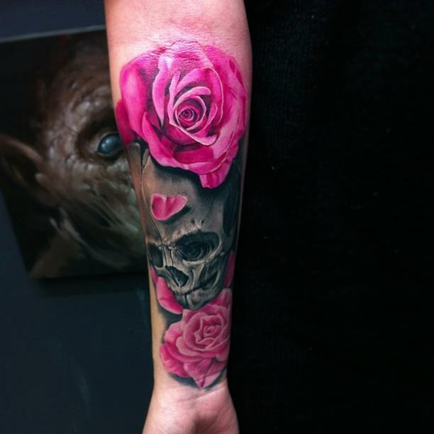 Vivid colors dark skull with pink roses forearm tattoo