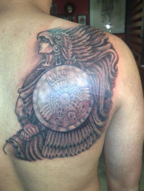 Warrior in indian headdress and with a shield tattoo on shoulder blsde