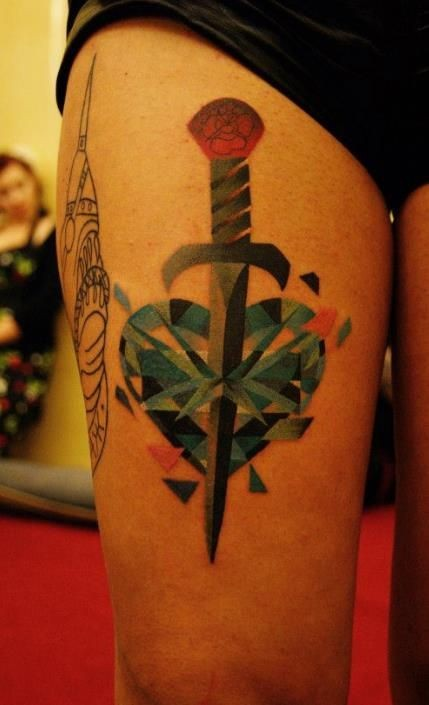 Watercolor dagger pierces heart tattoo on thigh