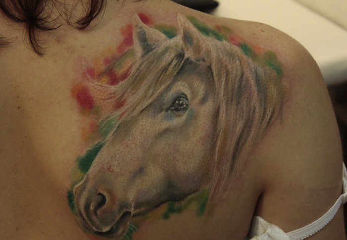 Watercolor horse head tattoo on shoulder blade