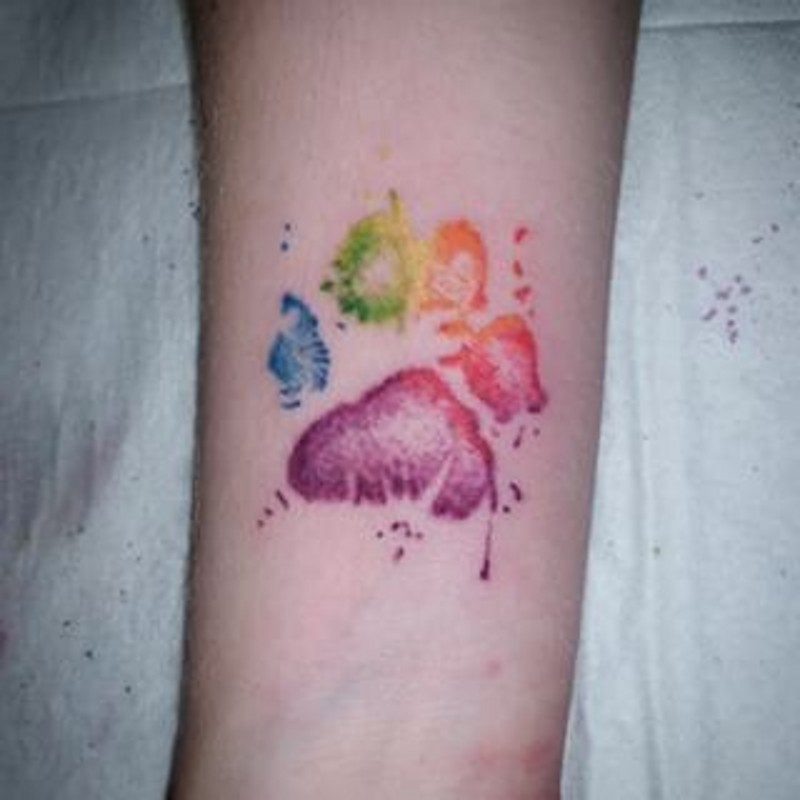 Watercolor like little colored animal print tattoo on arm