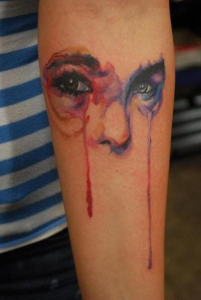 Watercolor like mystical colored eyes tattoo on arm