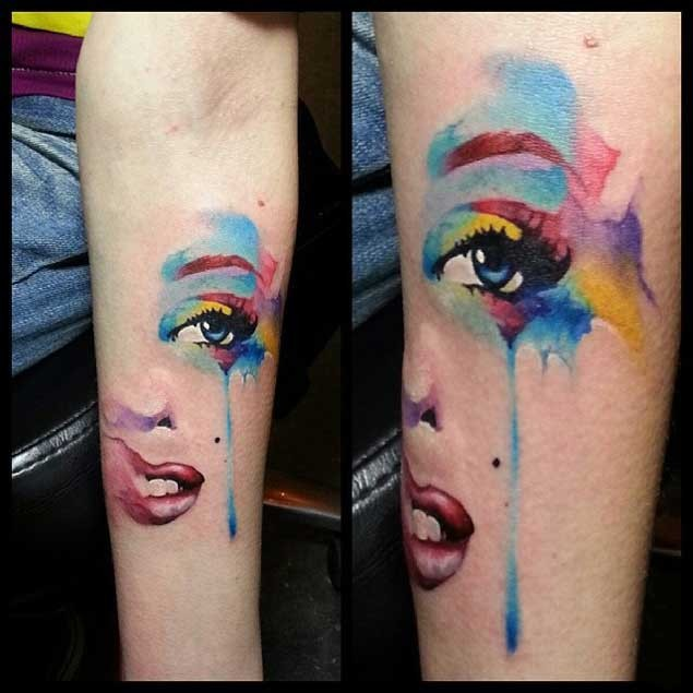 Watercolor like painted and colored tattoo on woman face parts