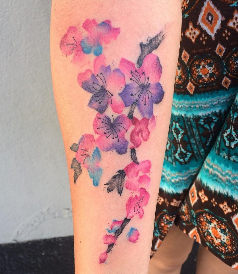 Watercolor painted simple designed beautiful flowers tattoo on forearm zone