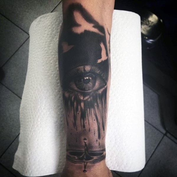 Watercolor style black ink natural looking human eye tattoo on forearm