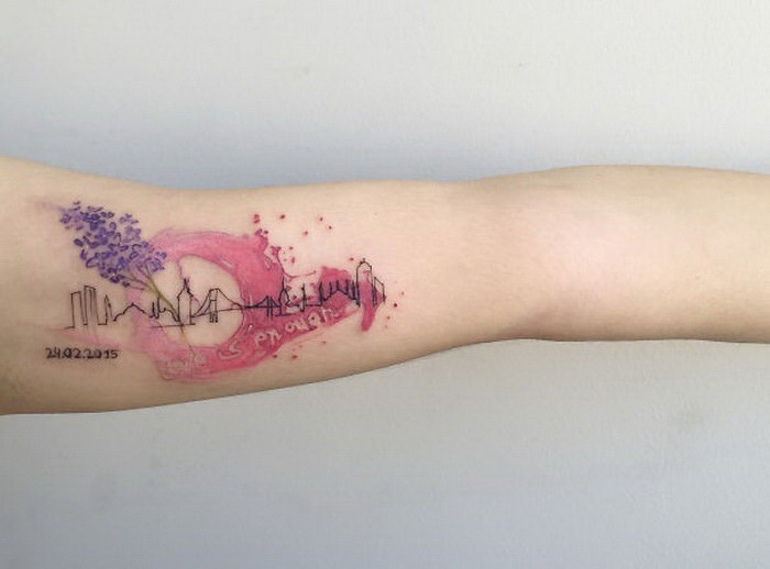 Watercolor style colored arm tattoo of city sights and numbers