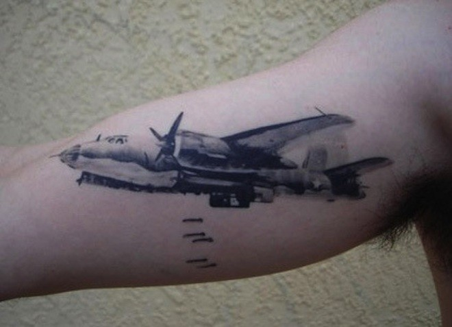 Watercolor style colored biceps tattoo of big bomber plane