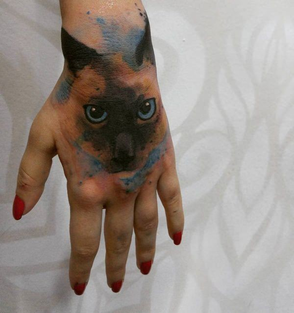 Watercolor style colored hand tattoo of cat face