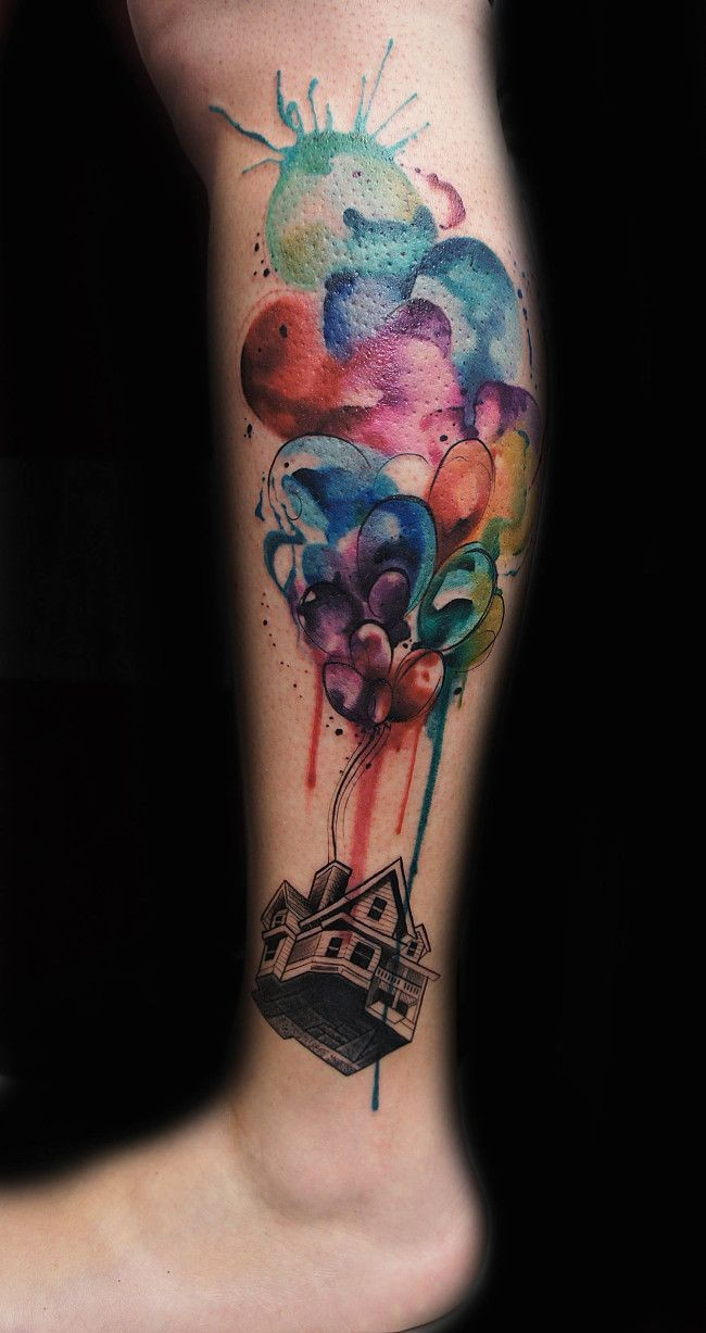 Watercolor style colored leg tattoo of flying balloons with house