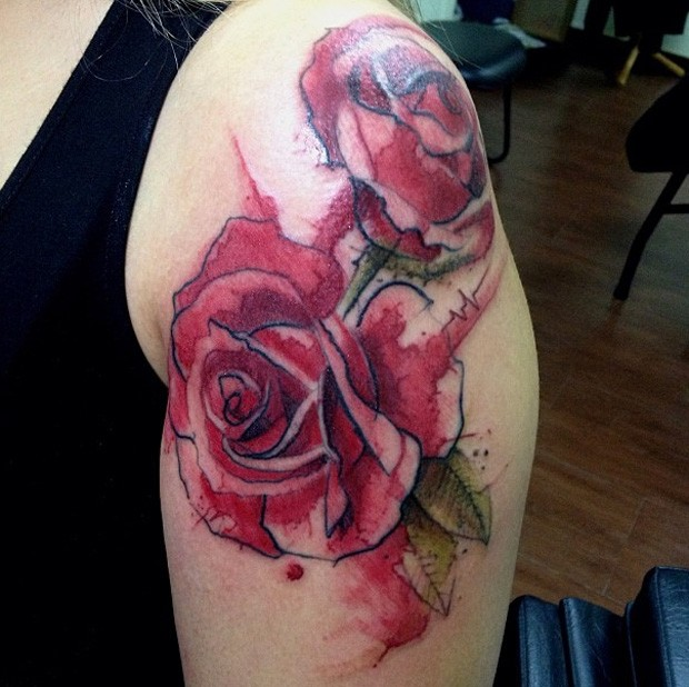 Watercolor style colored shoulder tattoo of big roses