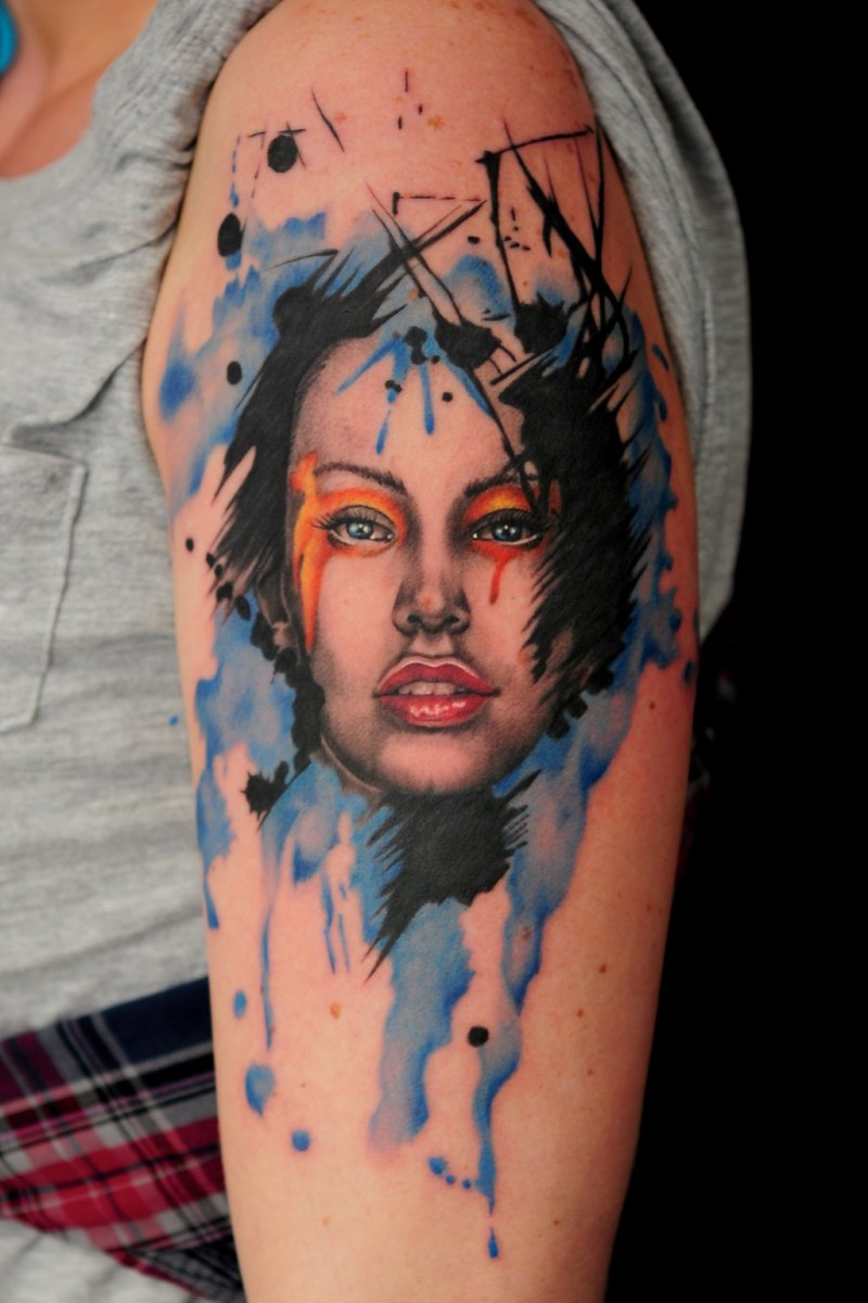 Watercolor style colored shoulder tattoo of woman face with makeup