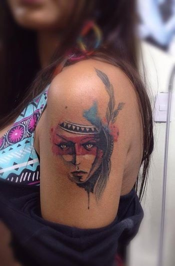 Watercolor style colored shoulder tattoo of Indian woman with feather