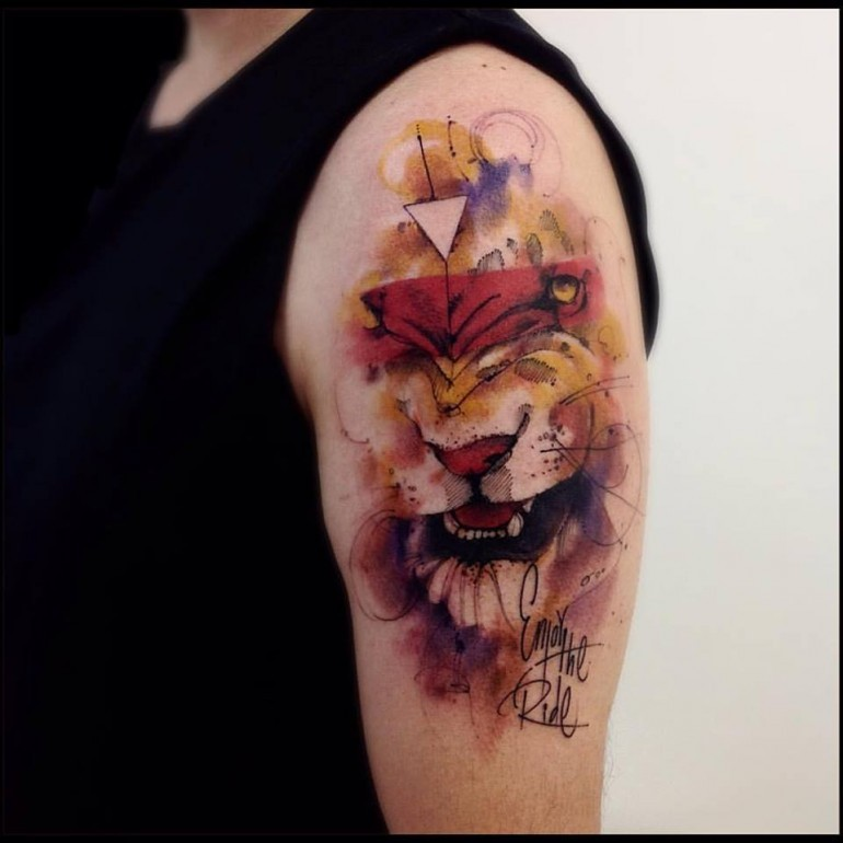 Watercolor style colored shoulder tattoo of lion with lettering