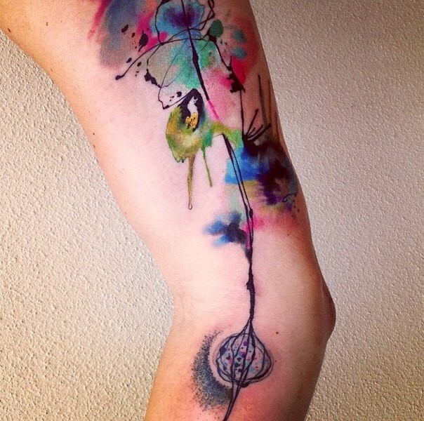 Watercolor style colored sleeve tattoo of flower