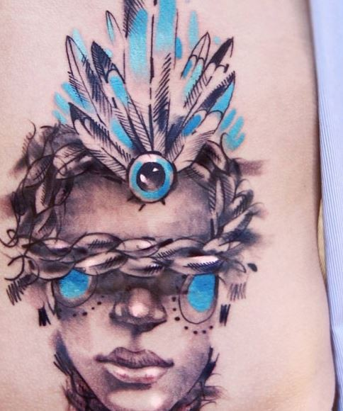 Watercolor style colored tattoo of human face with chain and feather