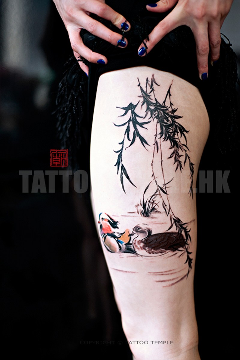 Watercolor style colored thigh tattoo of swimming birds and tree branches