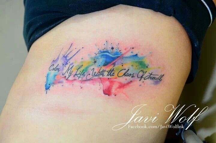 Watercolor style colored thigh tattoo of small lettering