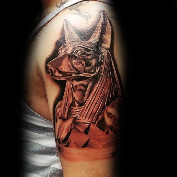 Watercolor style cool looking shoulder tattoo of Egypt God statue
