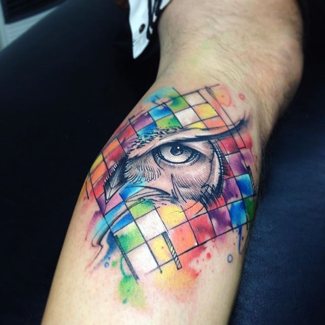 Watercolor style impressive looking leg tattoo of owl eye with geometrical figures