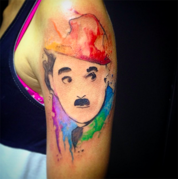 Watercolor style nice looking shoulder tattoo of Charlie Chaplin