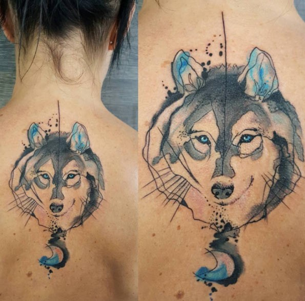 Watercolor style nice looking upper back tattoo of wolf portrait