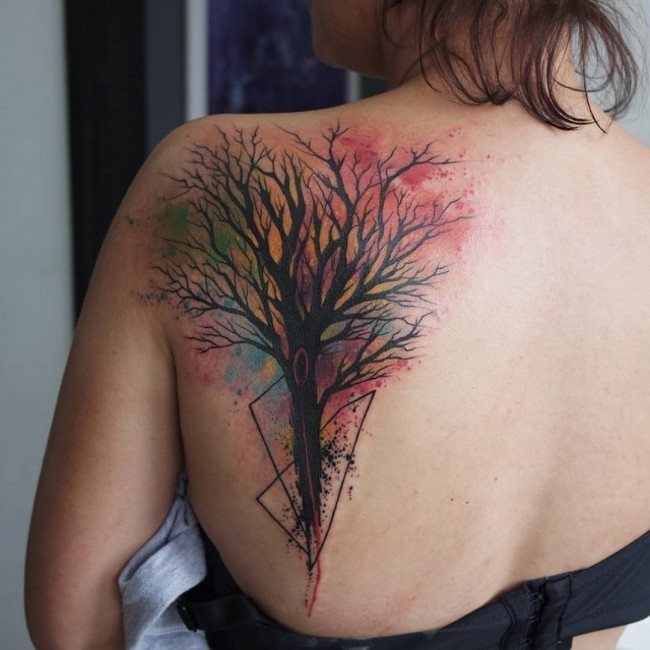 Watercolor style painted colorful tree tattoo on back with black triangle