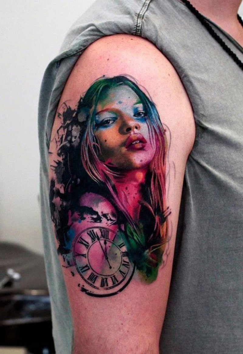 Watercolor style painted multicolored woman portrait tattoo on shoulder with old clock