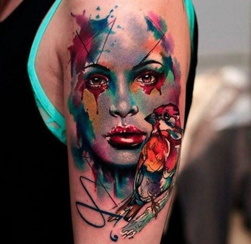 Watercolor style painted shoulder tattoo of woman&quots portrait and little bird