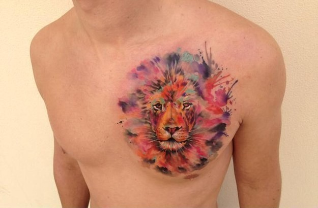 Watercolor lion head tattoo on chest