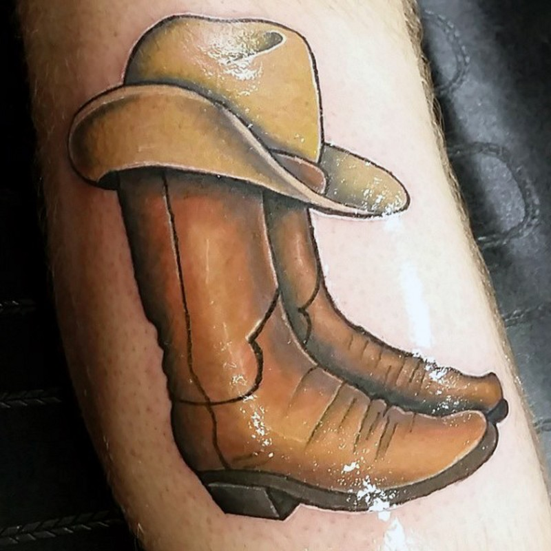 Western style colored big cowboy boots with hat tattoo on arm