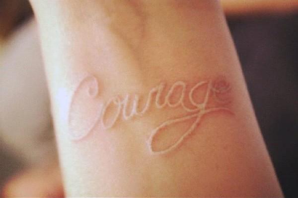 Tatuaje en la muñeca, palabra valor de tinta blanca