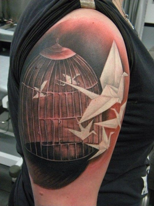 White origami birds flying out of cage  tattoo on shoulder