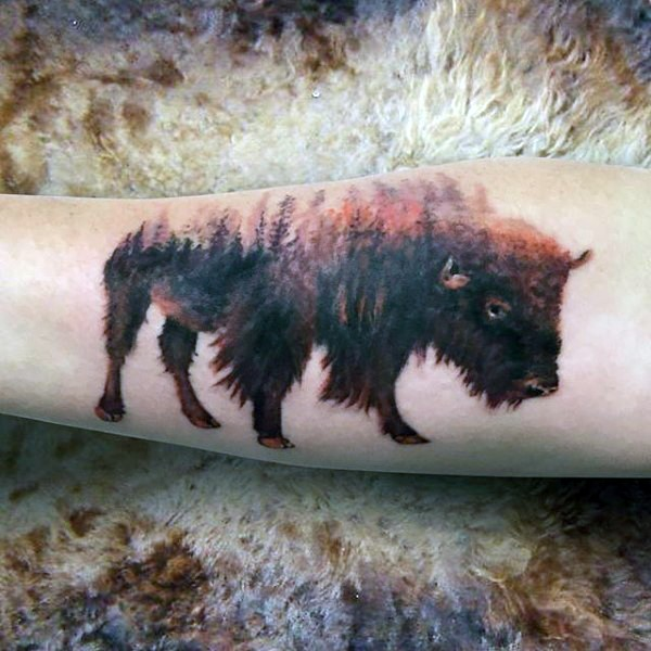 Wild bull shaped arm tattoo stylized with colored forest