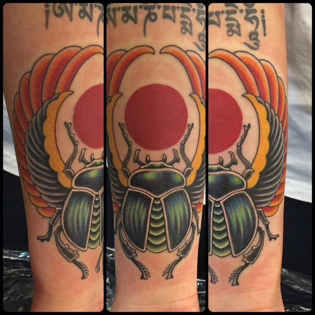 Winged Scarab and red sun Egyptian style colored forearm tattoo