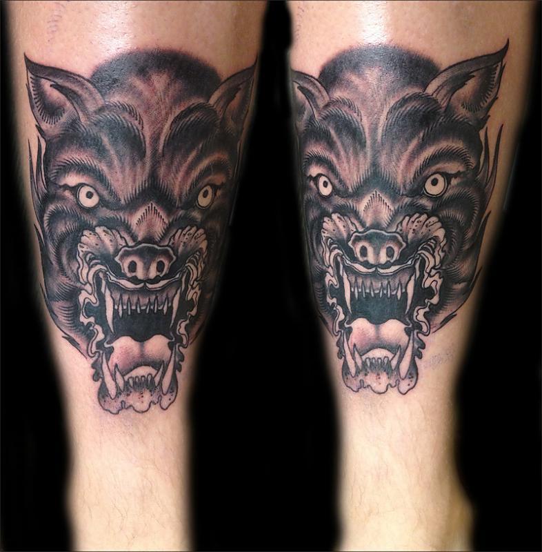Tatuaggio spaventoso sulla gamba la faccia del lupo con la bocca spalancata
