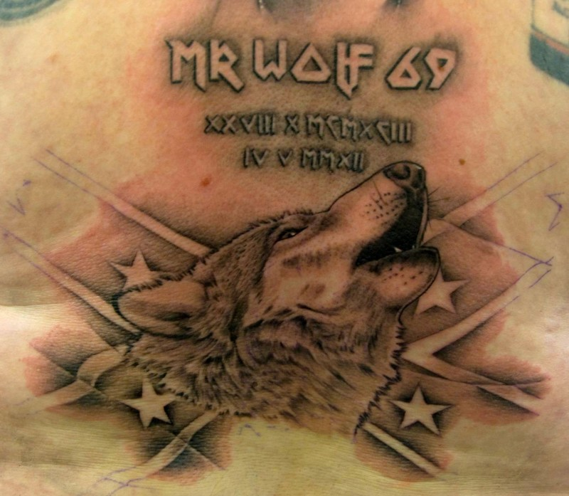 Wolf with an american flag and inscription tattoo on chest