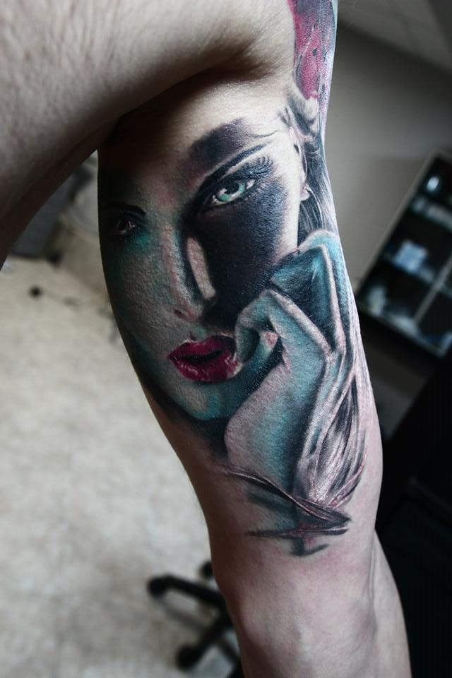 Woman face tattoo on arm